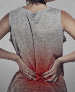 young woman with backache lower back pain colored in red isolated on gray background