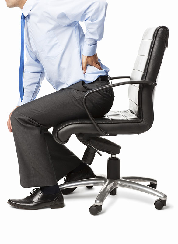Midsection of businessman with backache sitting in an office chair. Vertical shot. Isolated on white.