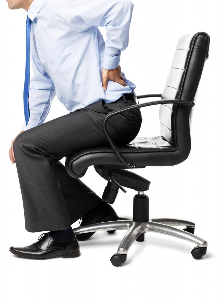 Midsection of businessman with backache sitting in an office chair. Vertical shot. Isolated on white. CSST