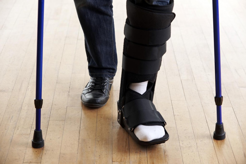 Close Up Of Man Walking With Crutches And Cast